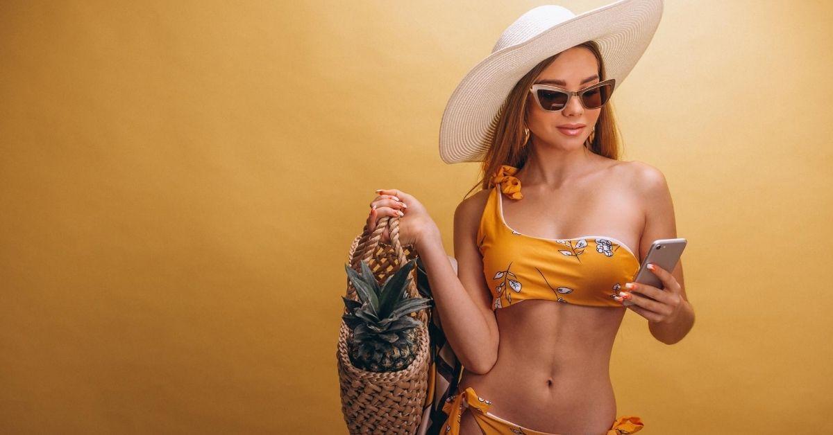 žena s plážovou taškou, klobúkom a okuliarmi